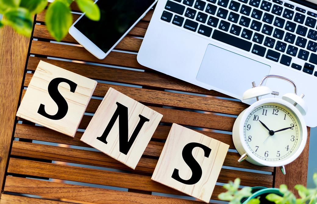 PCと携帯と目覚まし時計と「SNS」と書かれた木のブロック