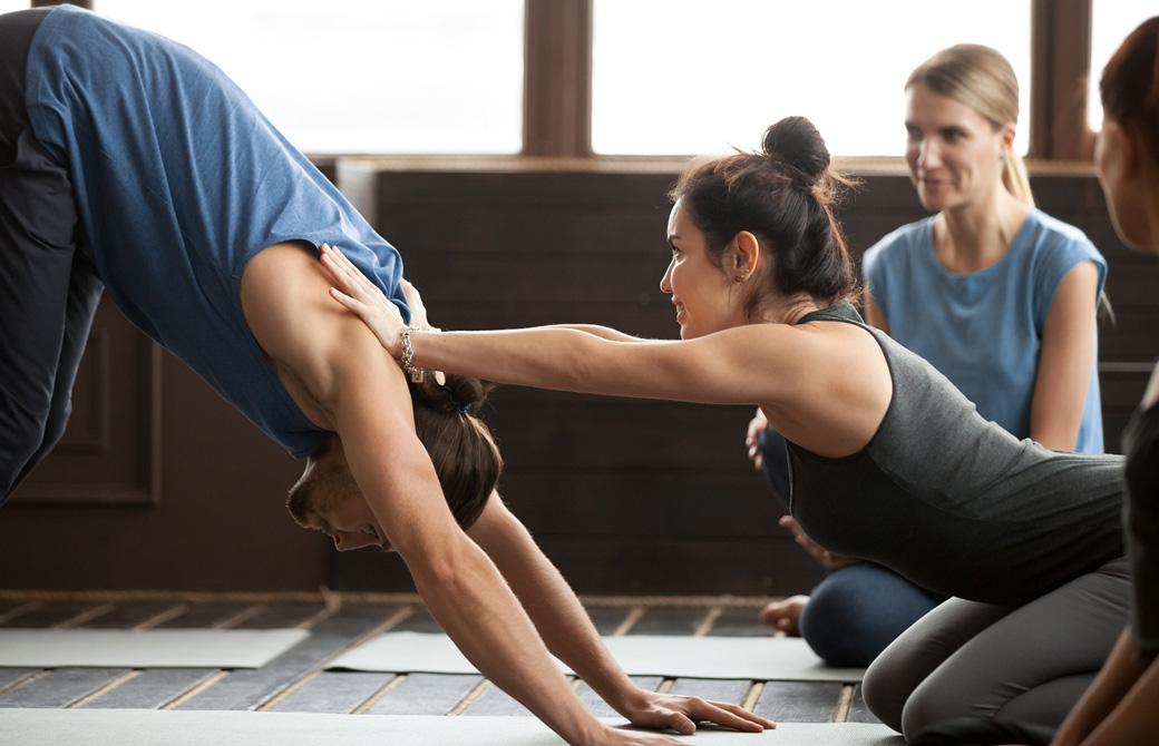 若い女性が男性生徒の肩を押さえてダウンドッグをアジャストしている