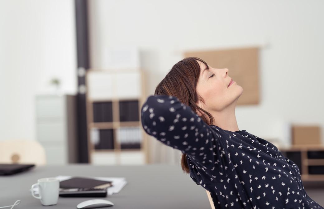 仕事中に疲れて椅子で背中のストレッチをしている女性