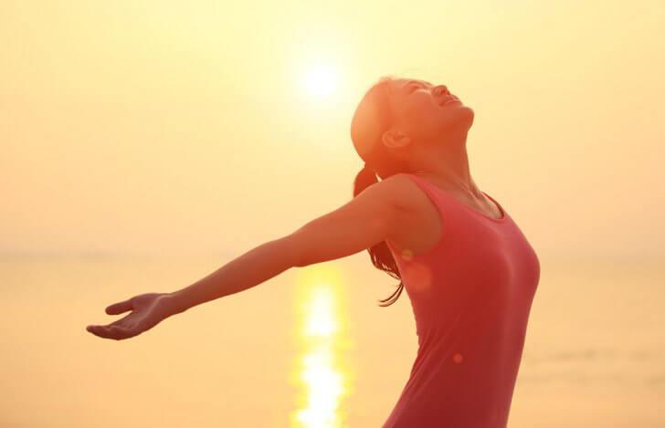 夕日をあびて両手を広げて空をあおいでいる女性