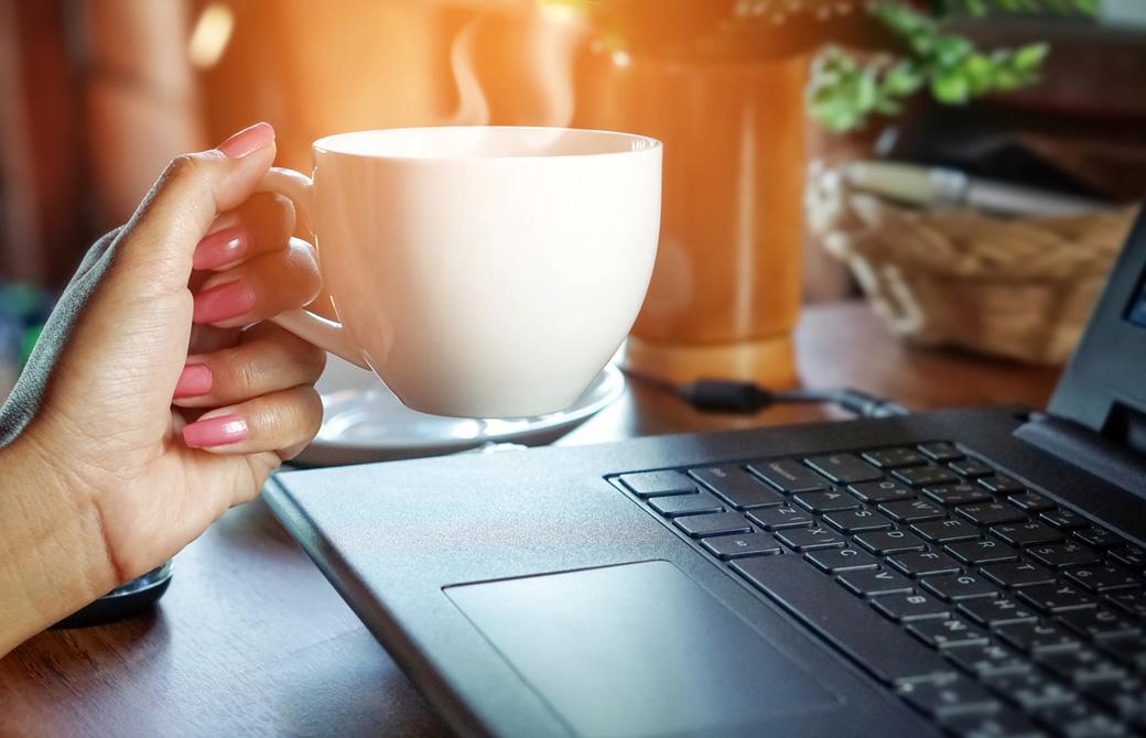 PCの前で湯気の出るコーヒーカップを持っている女性の手元