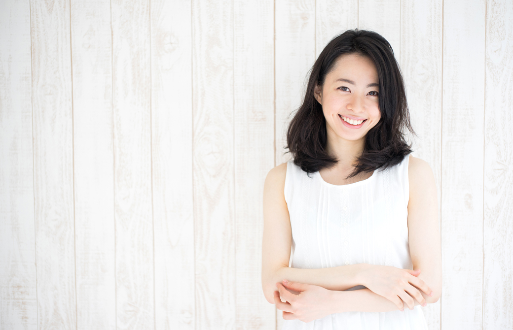 白い壁を背にして白いワンピースの女性が肘を組んで微笑んでいるウエストアップの写真
