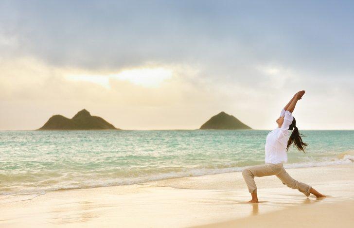 ハワイのラニカイビーチでヨガポーズをする女性