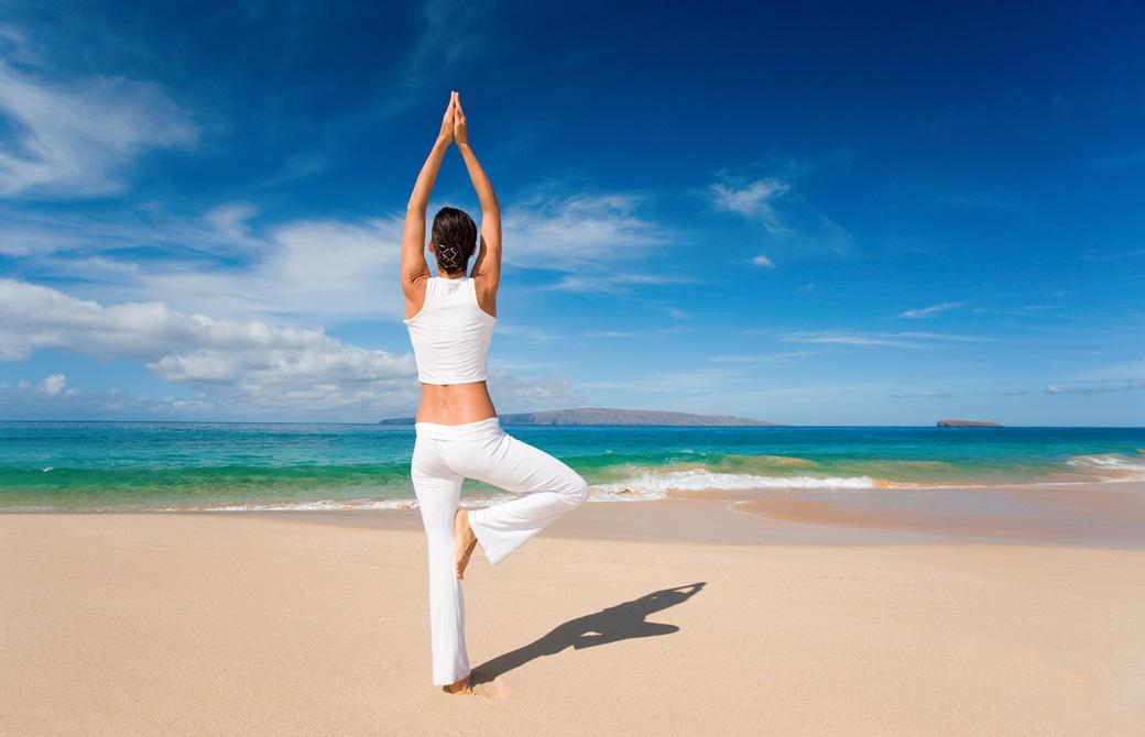真っ青な海に向って砂浜で木のポーズをする女性