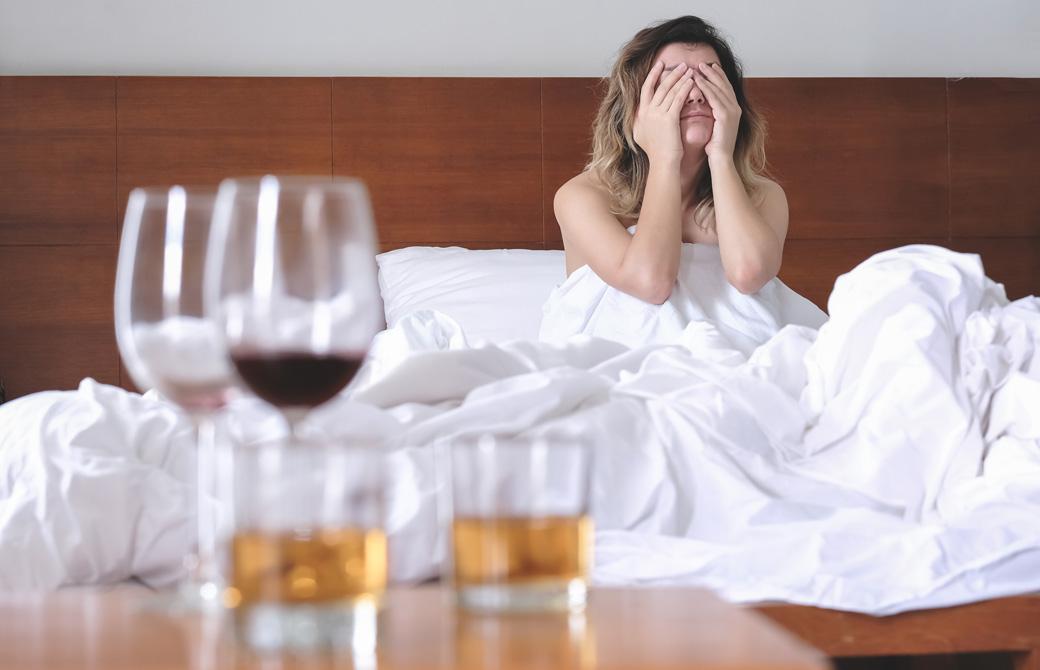 二日酔いでベッドの上で顔を覆っている女性とテーブルの上の飲み残しのお酒のグラス