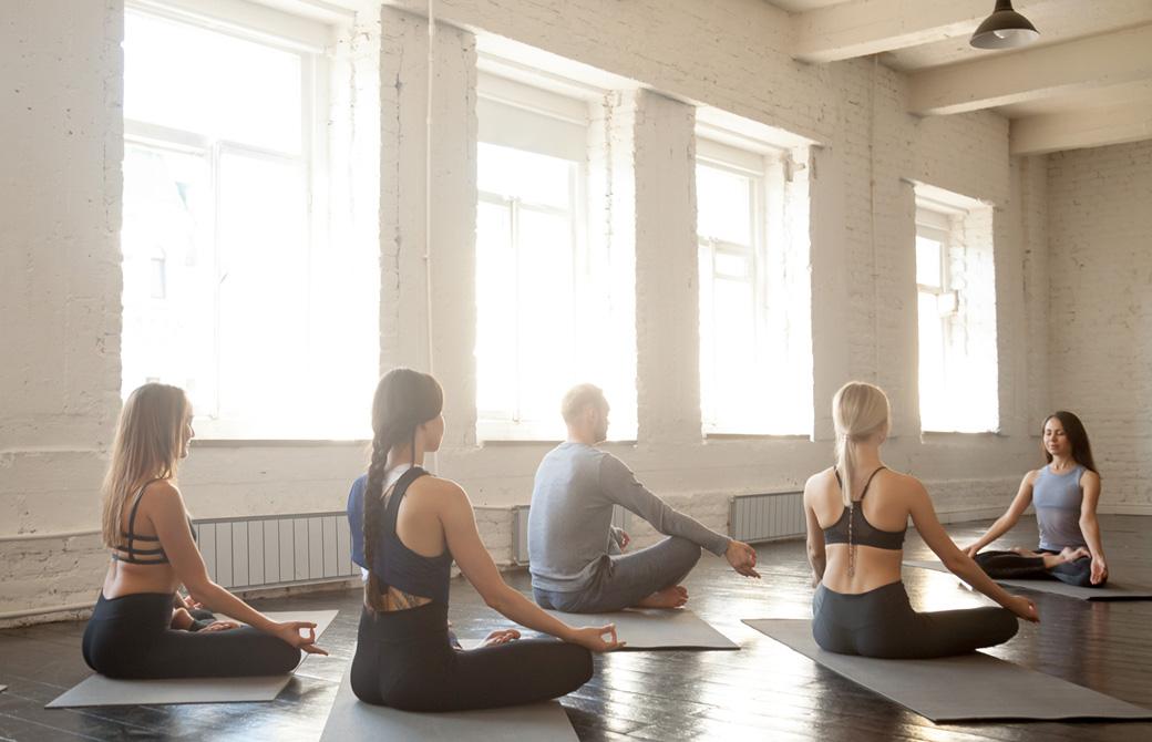明るいヨガスタジオで生徒とインストラクターが向き合って瞑想をしているところ