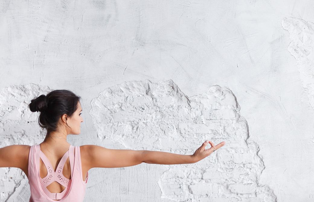 白い壁に向ってヨガポーズをとる女性の後ろ姿と横顔