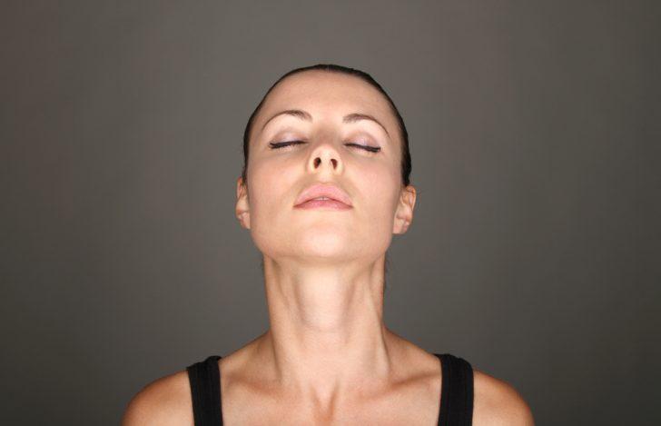 女性が目を閉じてあごを突き出し首元のストレッチをしている
