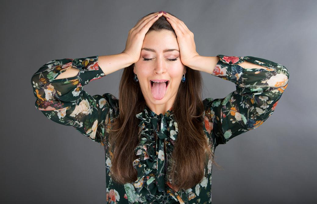 女性が頭をおさえて下を突き出し顔ヨガをしているところ