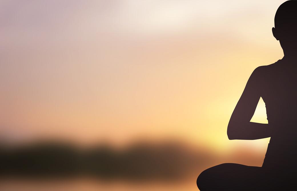 夕陽に向って手を合わせ瞑想する人のシルエット
