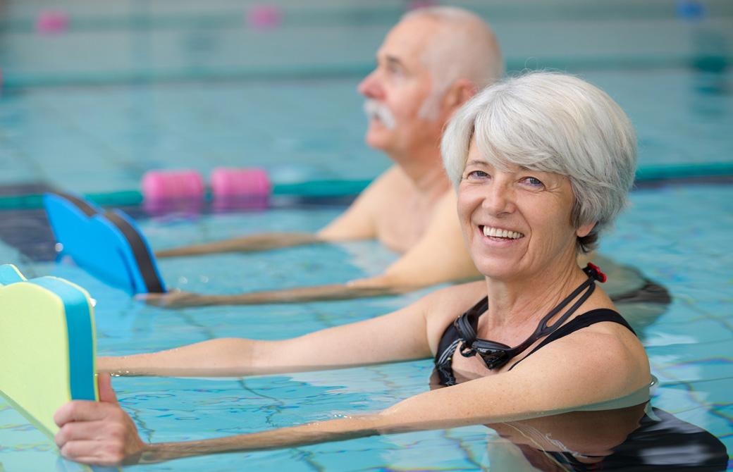 ビート板を持ってプールでエクササイズをする老夫婦