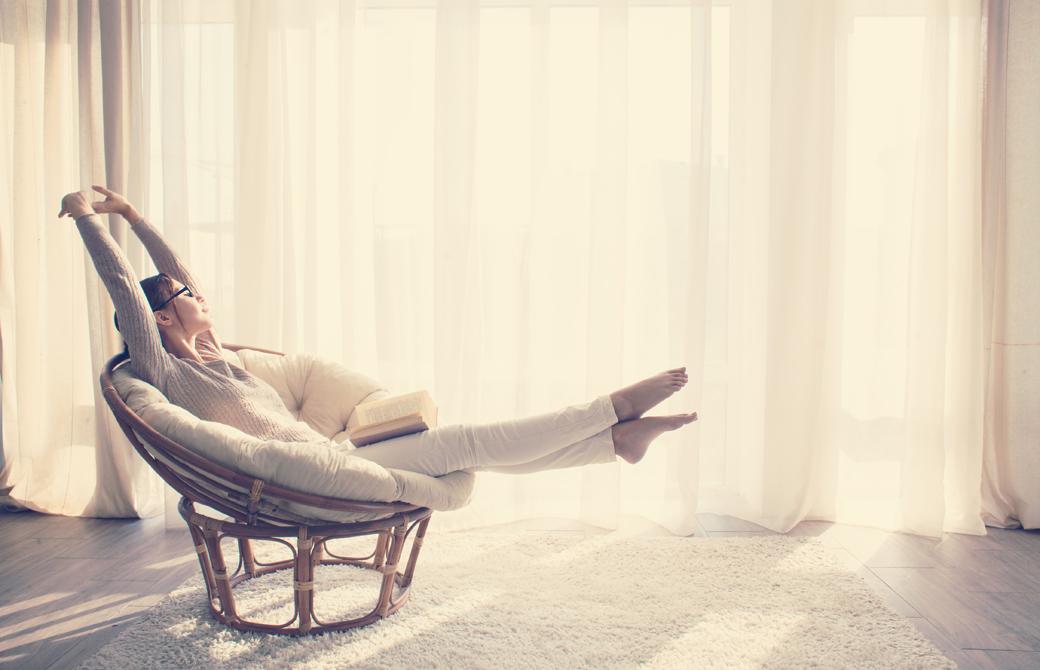 窓際でソファに座り大きく体を伸ばしている女性
