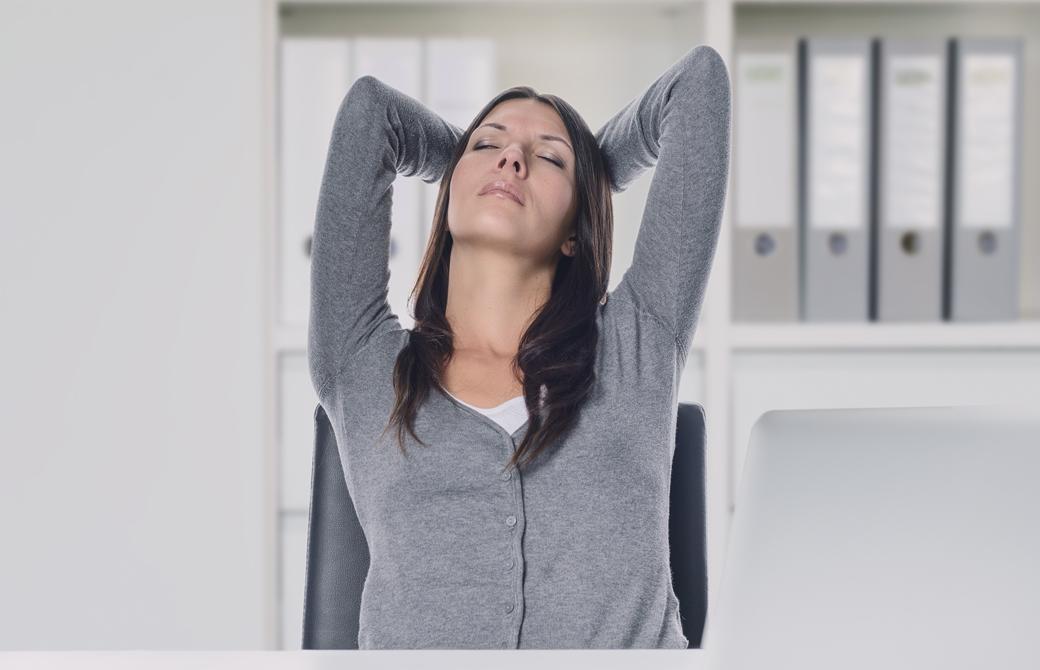 女性がデスクで座りながら後頭部をおさえてストレッチしている