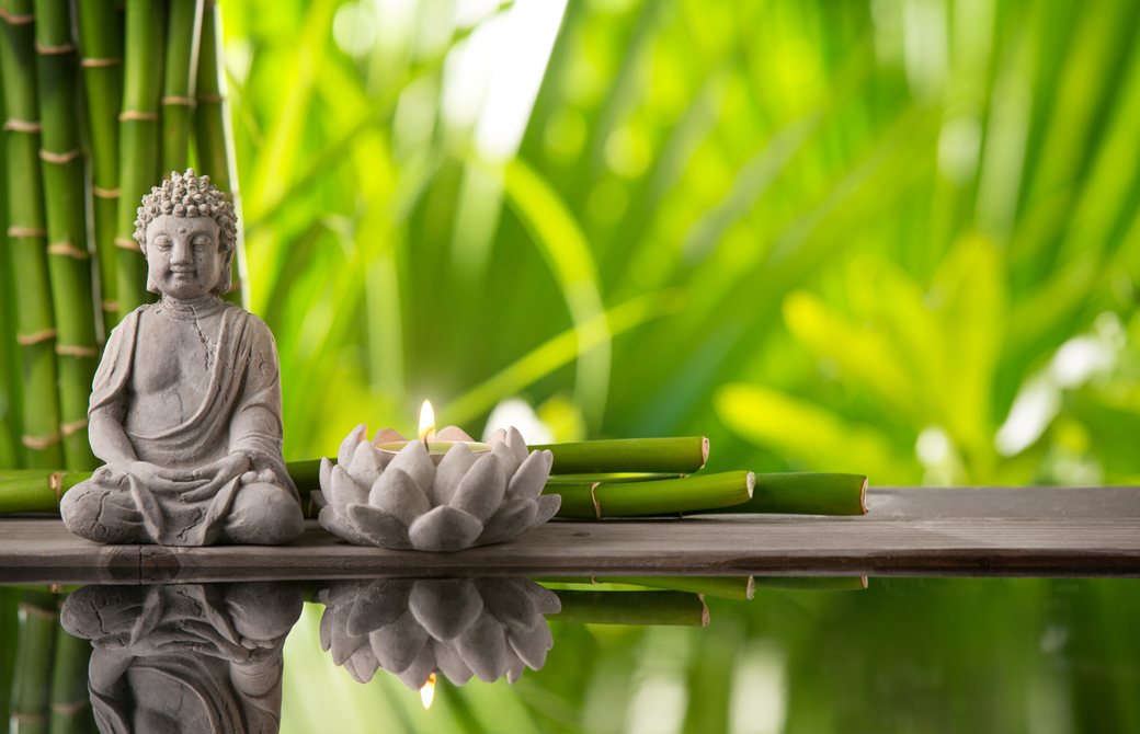 水辺に置かれた仏像と蓮の花の置物