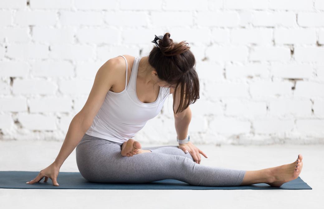 ヨガマットの上で片足を曲げて逆足に乗せ前屈みで痛そうな姿勢の女性