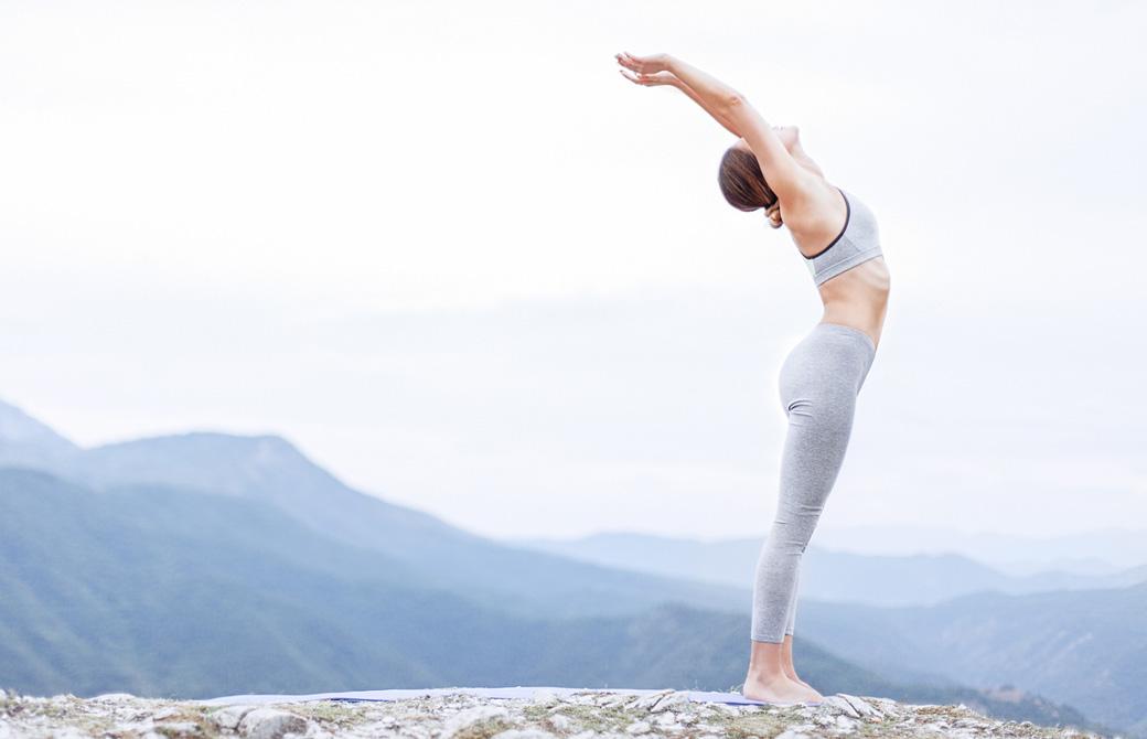 山を臨む屋外で心地よく腕を伸ばし立位の後屈をする女性