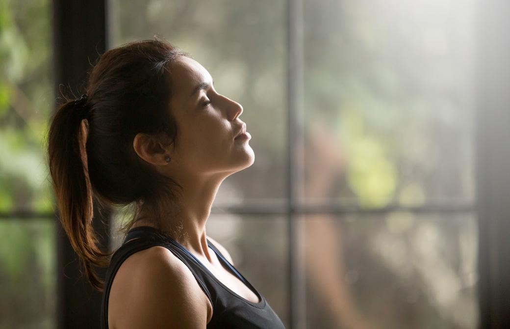 室内で目を閉じ呼吸をしている女性の横顔