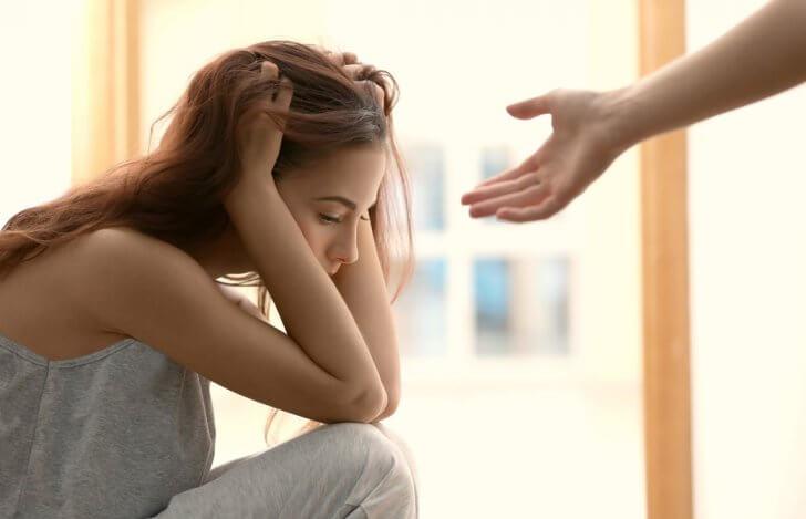 頭を抱えて悩んでいる様子の女性と誰かが彼女に手を差し伸べている