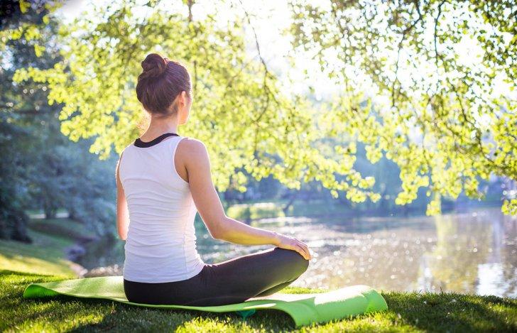木漏れ日の下、湖に向って瞑想をする女性の後ろ姿