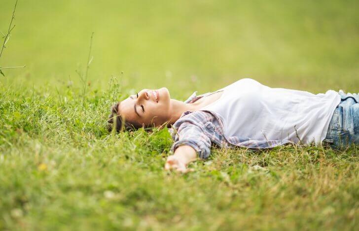 芝生で仰向けで気持ち良さそうに目を閉じ微笑んでいる女性