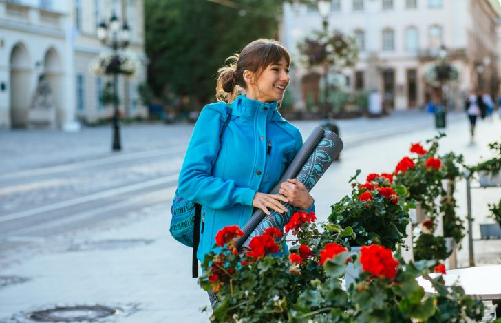 ヨガマットを持った青いジャケットを着ている女性がバラの生け垣の前で微笑んでいる