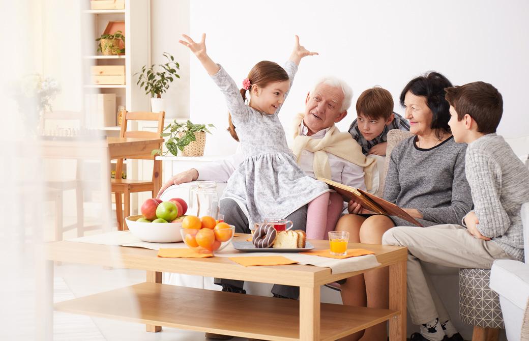 おじいちゃんおばあちゃんもそろった家族がソファで楽しそうに団らんしている