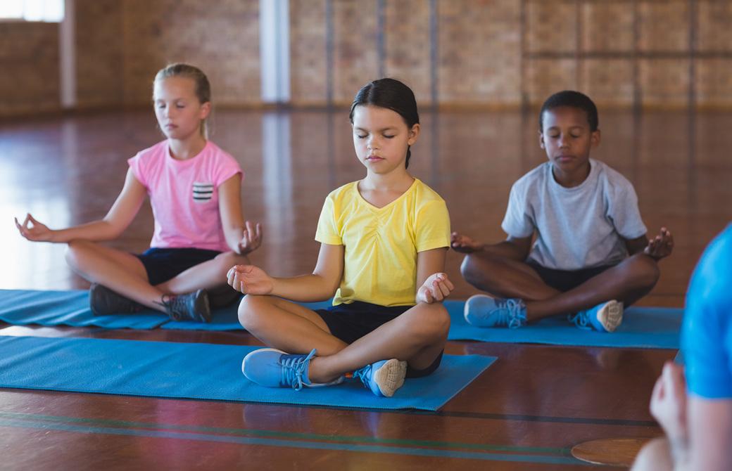 2人の少女と1人の男子が体育館のような場所で瞑想を練習している
