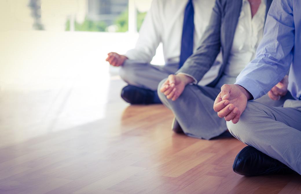 室内でスーツ姿の男性3人があぐらの姿勢で瞑想をしている