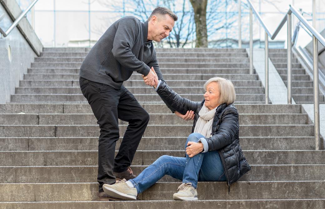 階段の途中で転んだ老婦とその腕を持ち助けようとしている男性