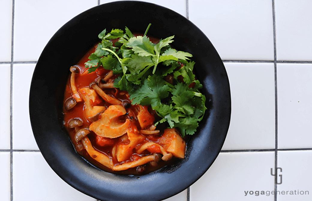 黒いお皿に盛り付けたレンコンとシメジ、お豆のメキシカン・チリ・スープ