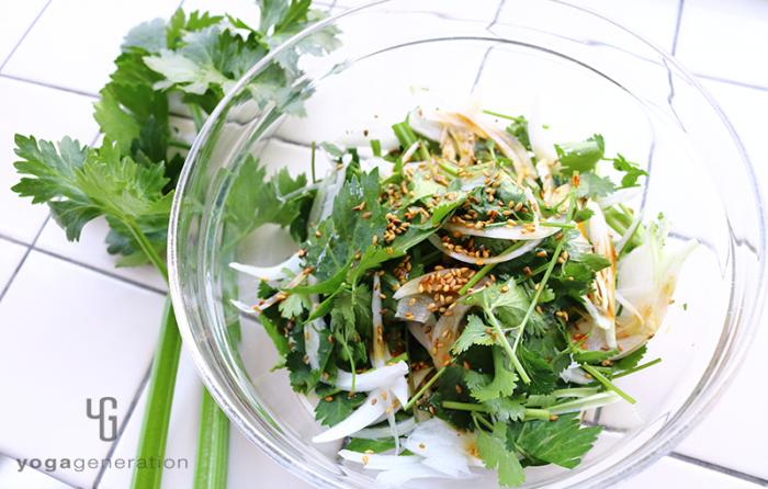 ガラスボウルに盛り付けたセロリと新玉ねぎ、パクチーのピリ辛ゴマサラダ