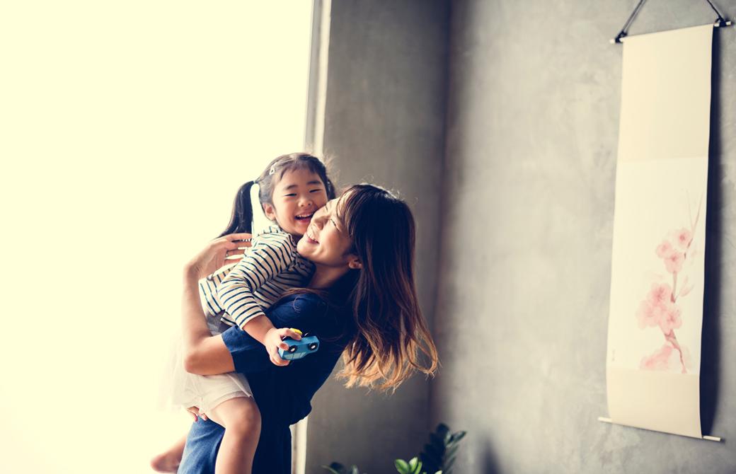 母親が少女を抱っこして微笑んでいるところ