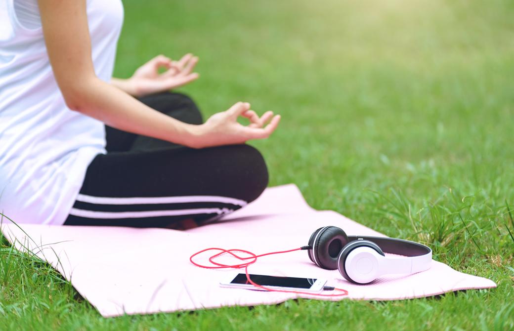 芝生の上であぐらの姿勢で瞑想をしている女性