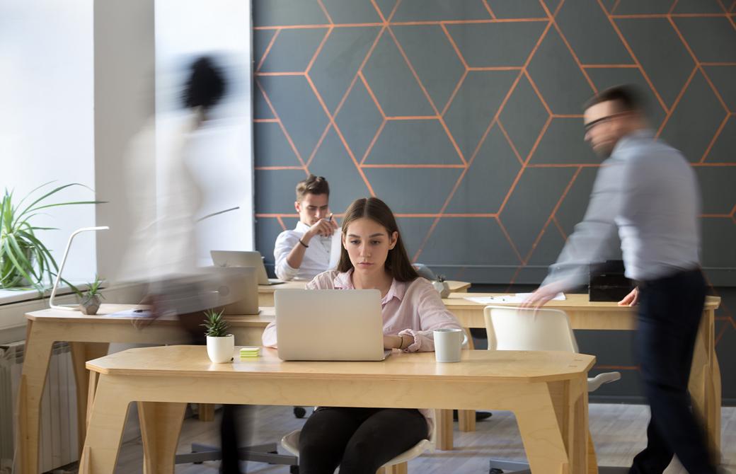 女性がオフィスのテーブルでPCに向って集中しているところ