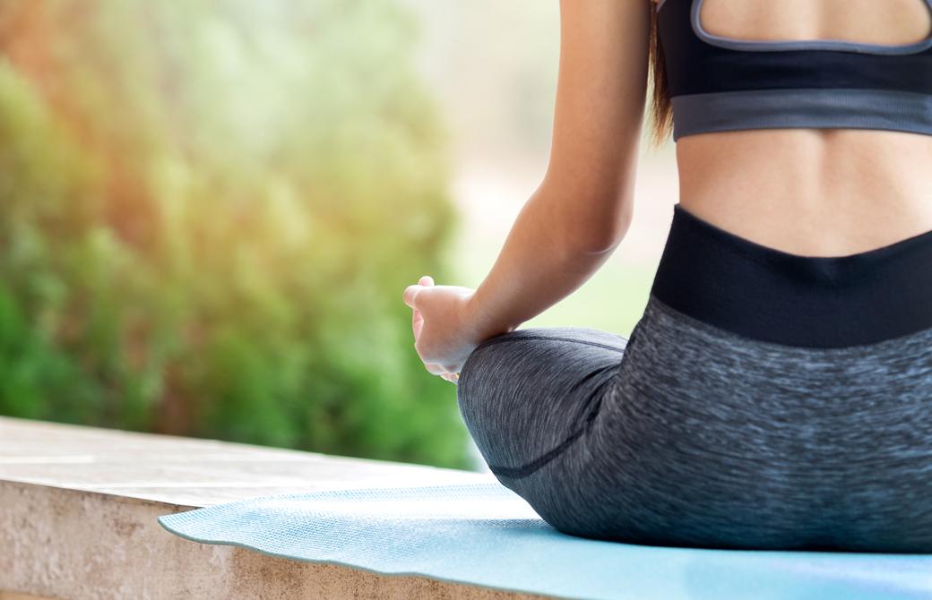 ロータスポーズで瞑想をする女性の腰から下