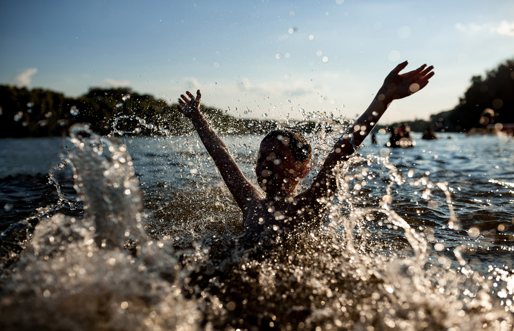 川で水遊びしている両腕を上げた少年