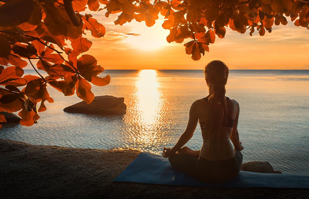 海辺でサンセットを受けて瞑想をする女性