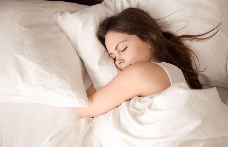 ベッドで心地良さそうに枕を抱いて眠る女性