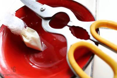 赤い皿に乗ったハサミと小さなビニール袋