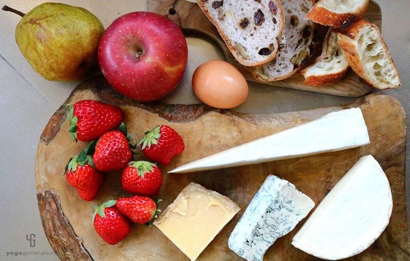 木製カットボードの上のチーズやフルーツやパン