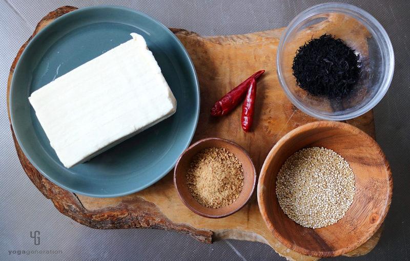 木製のカットボードの上の豆腐・ひじきなどの材料