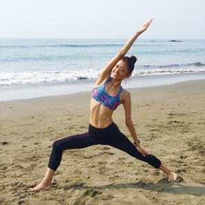 松本莉緒さんがヨガポーズをビーチでしている写真