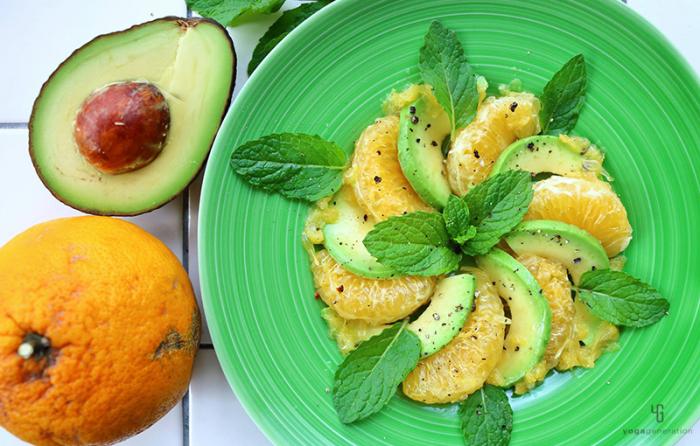 緑の皿に並べたアボカドと甘夏のサラダ