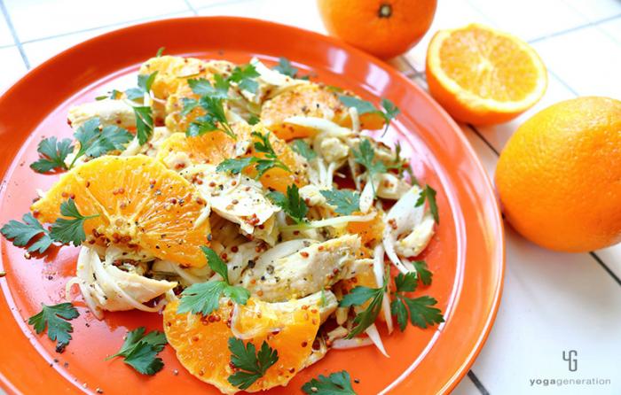 オレンジ色の皿に乗ったオレンジとチキンのサラダ
