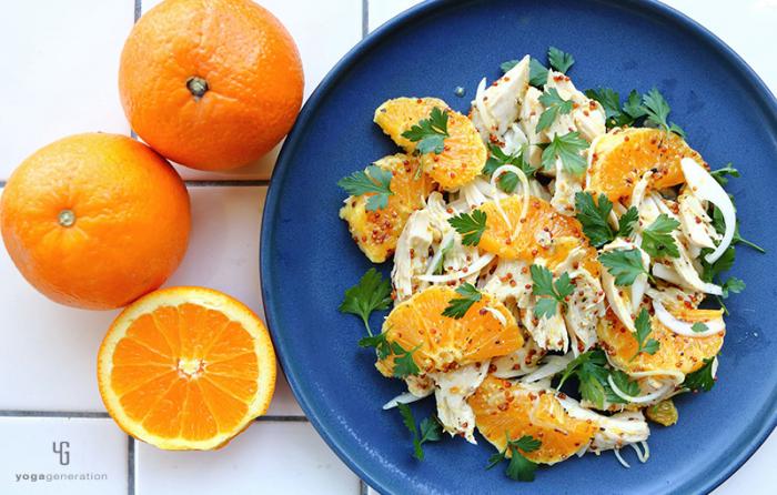 ネイビーの皿に乗ったオレンジとチキンのサラダ