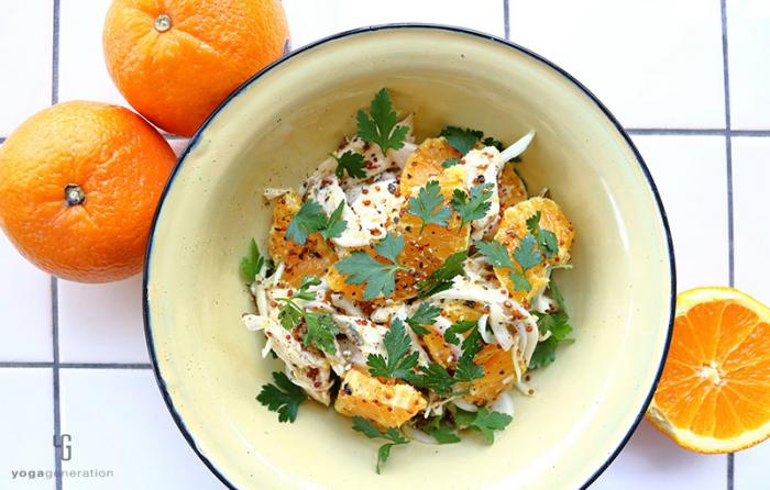 クリーム色の皿に乗ったオレンジとチキンのサラダ