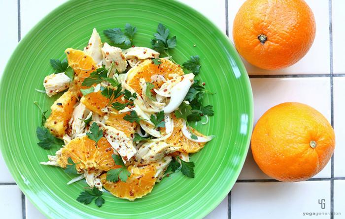 緑の皿に乗ったオレンジとチキンのサラダ