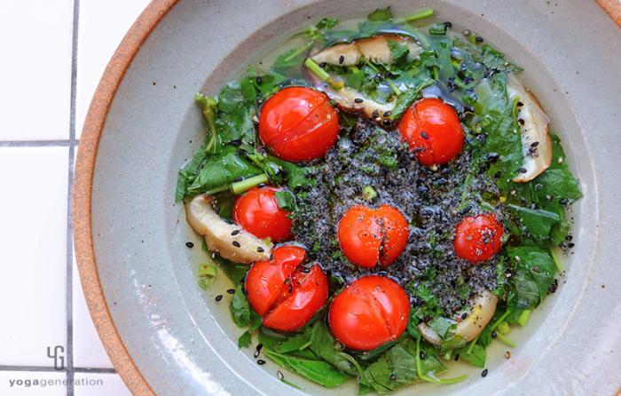 グレーの器にに入ったモロヘイヤとトマトの酸っぱいスープ
