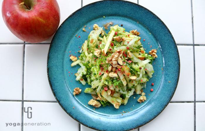 翡翠色の皿に盛り付けた白菜とリンゴとクルミのクリスピー・サラダ