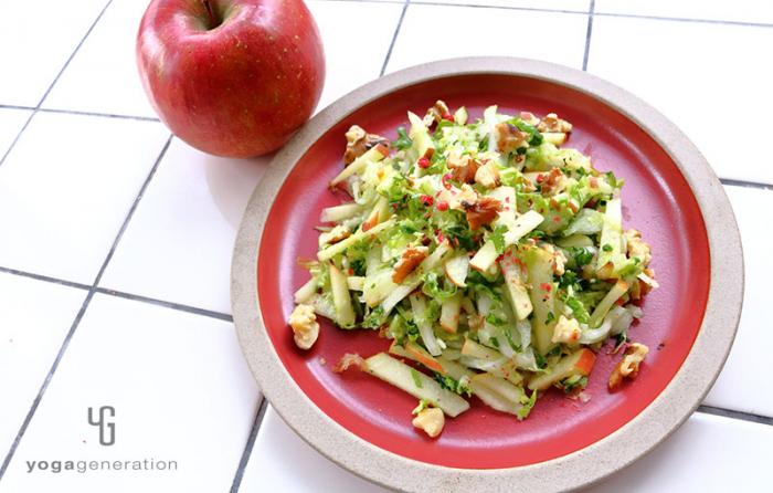 赤い皿に盛り付けた白菜とリンゴとクルミのクリスピー・サラダ